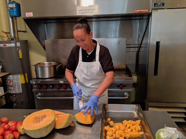 OTRS employee helps at Dorothy Day Soup Kitchen with cutting pumpkins