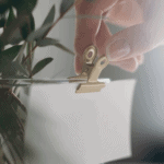 Hand clipping a ticket to a vase