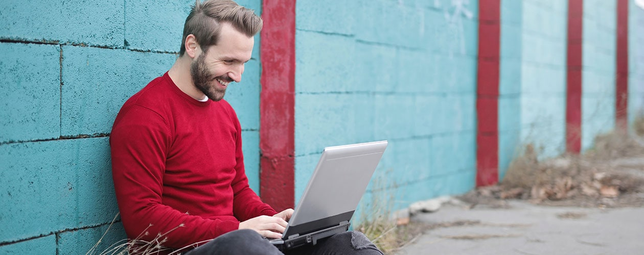 man sitting with laptop on the ground next to a wall