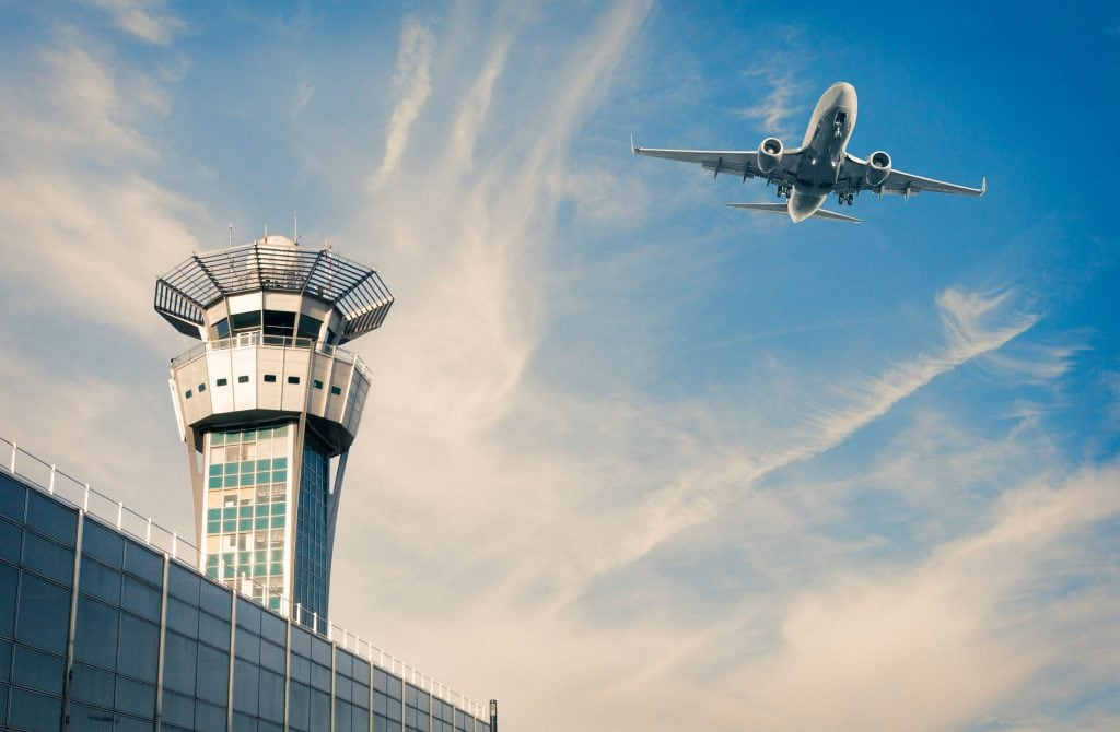 Airplane over airport and terminal with blue skies and soft clouds
