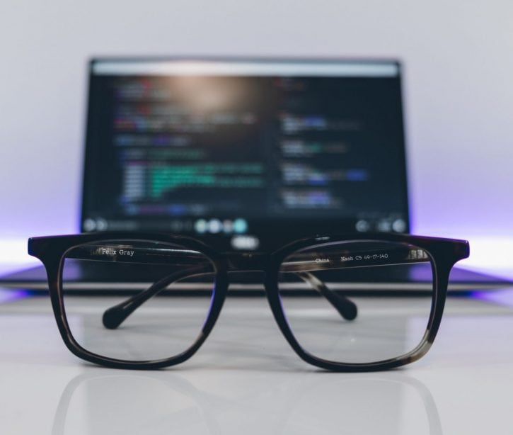 Glasses lying on a table in front of a laptop