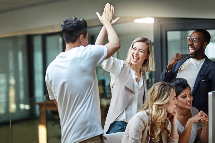 A joyful high-five in the office between man and woman while work colleagues look on