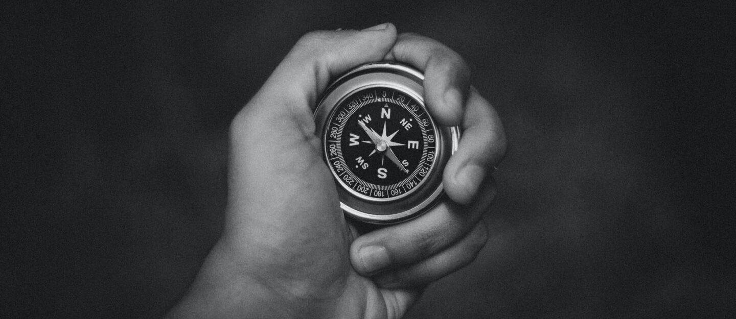 hand holds a compass
