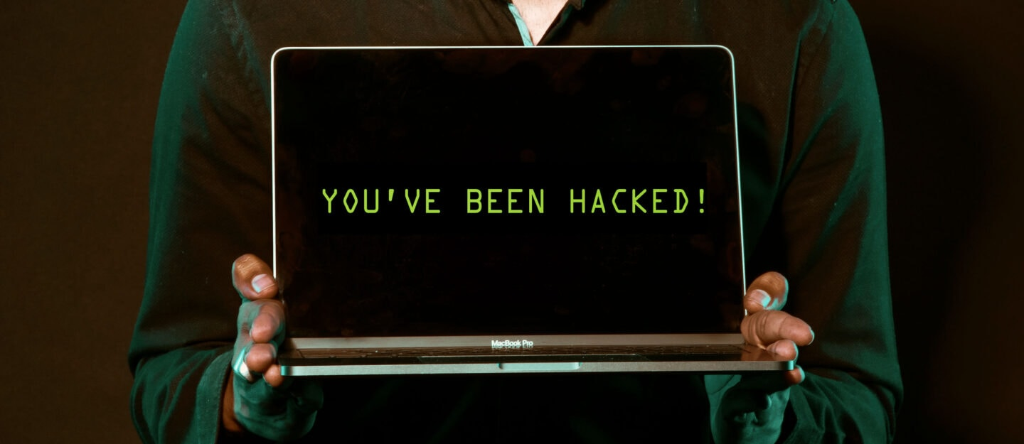 man holds laptop with text you've been hacked on screen