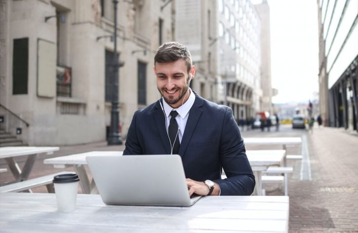 man sitting in front of a laptop smiling be successful with OTRS