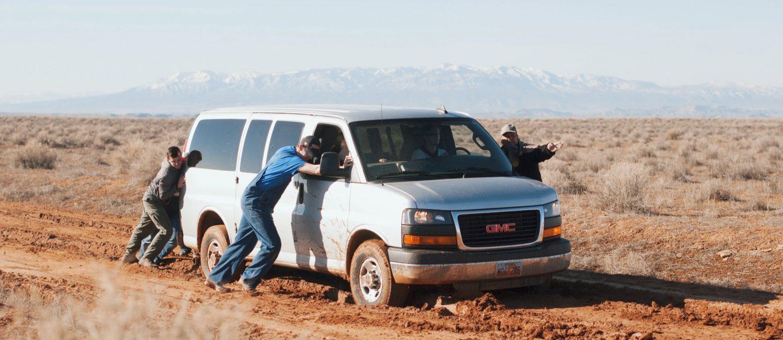 men pushing a car
