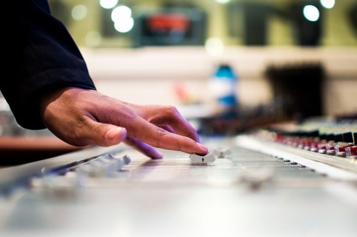 Hand sliding a controller on a mixing console