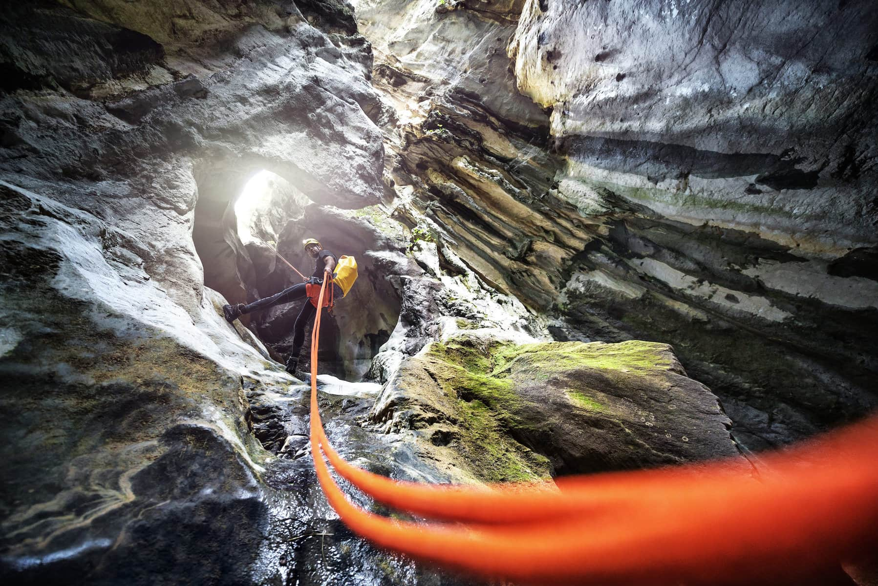 Cave climber secured by an orange rope sees sunlight
