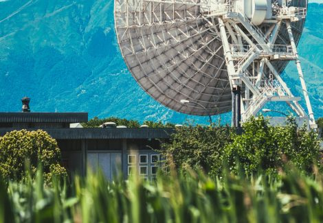 Large satellite in a lush green field faces mountains on a bright blue day. Positioned next to a single small house.