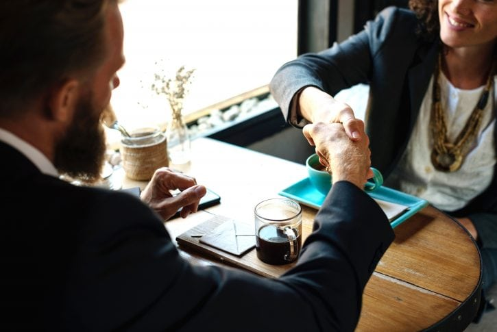 Handshake at a business meeting between a man and a woman both in suits