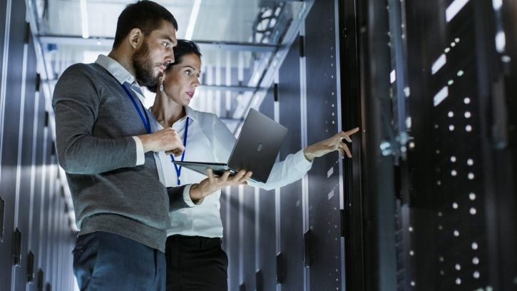 Woman and man with laptop stand in front of servers in a data center